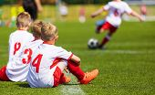 Постер, плакат: Young Boys Playing Football Match On A Pitch School Football Tournament For Youth Teams Football S