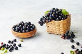 Freshly picked blackcurrants. Blackcurrants in a bowl and beside a small wicker basket of fresh blac poster