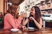 Happy Female Friends Having Coffee In Outdoor Cafe In Summer On The Street. Women Chatting And Chill poster