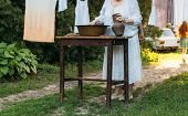 An Elderly Woman Is Washing Clothes In The Garden. In White Vintage Clothing. Country Life. Clothes  poster