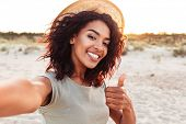 Close up of cheerful young african girl in summer hat taking a selfie at the beach and showing thumb poster