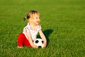 The Smiling Little Cute Baby Girl Is Playing With Small Soccer Ball For Children On Green Grass Play poster
