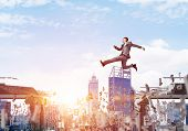 Businessman Jumping Over Gap With Flying Letters In Concrete Bridge As Symbol Of Overcoming Challeng poster
