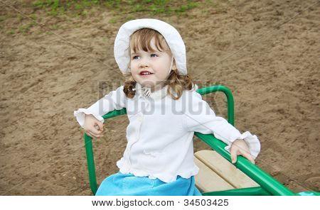 kleine Mädchen tragen weiße Panama Fahrten auf kleinen Karussell auf Spielplatz