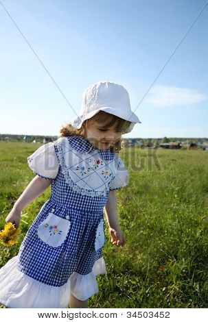 Happy Little Girl Wearing Dress And White Panama Walks On Green Field