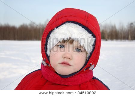 Little Serious Girl Stands Near Forest At Winter And Looks Into Camera