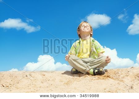 Happy Child Positive Think, Boy Sitting in Yoga Lotus position over blue sky