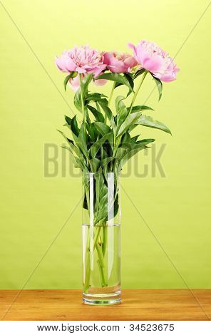Three pink peonies in vase on wooden table on green background