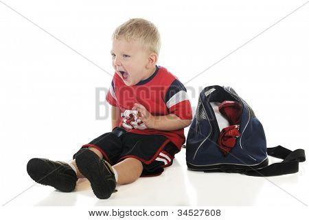 A young preschool athlete, sitting by his gym bag yelling at his team mates.  On a white background.