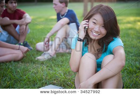 Young Asian girl talking on phone outside