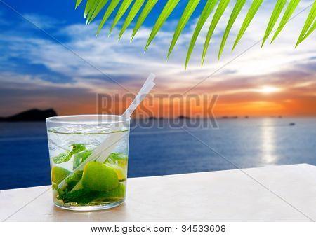 Ibiza cala Conta Conmte sunset with Mojito drink cocktail [ photo-illustration]