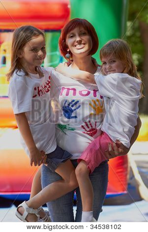 Mother Holding Her Daughters In Arms Outdoors