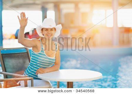 Lächelnde Frau am Schwimmbad Bar salutieren