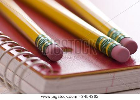 Three Pencils On Notebook
