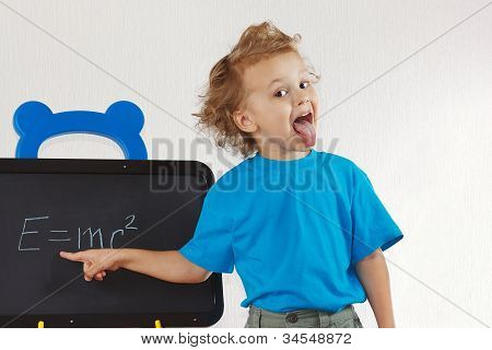 Little boy shows tongue like Einstein near formula on a blackboard