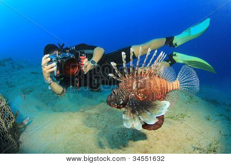 Female underwater photographer takes a photo of a Lionfish
