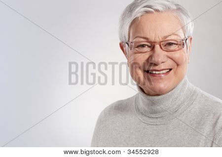 Portrait of elderly lady smiling in glasses and polo-neck sweater.