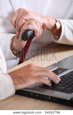 old women hands holding a walking stick and a manly hand typing on a keyboard