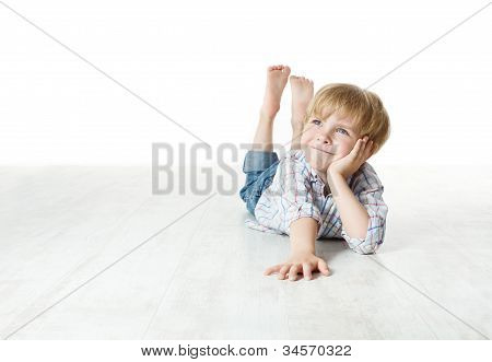 Thinking Smiling Little Boy Lying Down On Floor And Looking Up To The Side