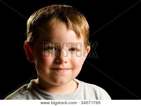Portrait of mischievous smirking child isolated on black