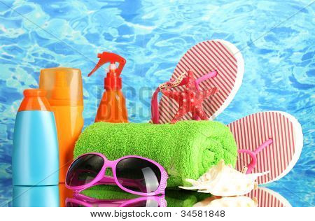 bright beach accessories, on blue sea background