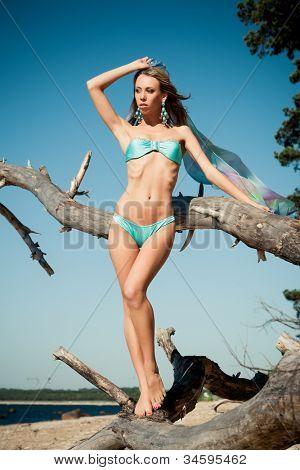 Young woman in bikini posing near a snag on a beach