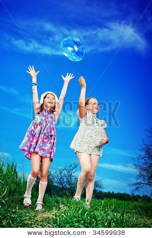 Two happy girls playing with big bubbles in a park.