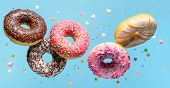 Flying Donuts With Sprinkle On Blue Background. poster