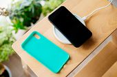Black Smartphone And Mint Silicone Case Is Charged From A Wireless Charger. The Mobile Phone Is Char poster
