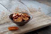 Dried Apple Slices In A Ceramic Plate Stand On A Textured Wooden Board, Next To A Dried Apple In The poster
