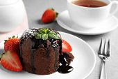 Delicious Warm Chocolate Lava Cake With Mint And Strawberries On Table, Closeup poster