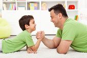 Father and son arm wrestling at home - childhood and parenting