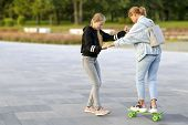 Young Mother Exercises On A Skateboard On The Street, Her Daughter Helps Her Mother Ride A Skateboar poster