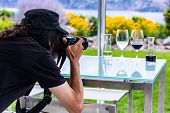 Man Photographer With Long Hair Wearing Black Rear Back View As He Takes Photos Of Wine Glasses With poster