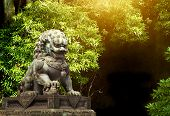 Bronze statue of a lioness with a lion cub in the morning forest. Chinese lion sculpture in jungle.  poster