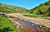 pic of swales  - Rocky riverbed and clear water of the River Swale as it flows along the valley floor between the rolling hills of the Yorkshire Dales England - JPG