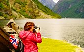 Female Tourist With Norwegian Flag Near Old Wooden Viking Boat On Fjord Shore, Taking Photo With Cam poster