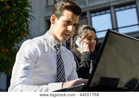 Young Businessman Typing In A Laptop Computer In Urban Background