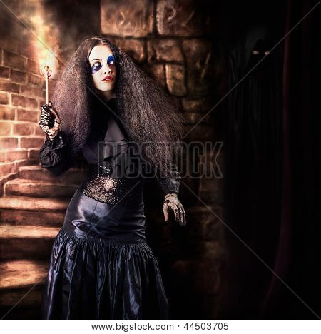 Female Jester Walking Inside Dark Castle Stairwell