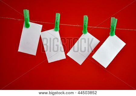 Blank notes hanging clipped on the rope in front of red background