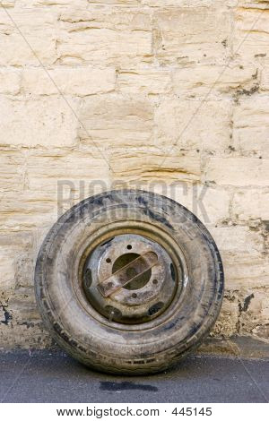 An Old Tyre Leaning Against A Wall By The Roadside