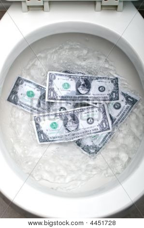 Dollar Bills Being Flushed Down A White Toilet