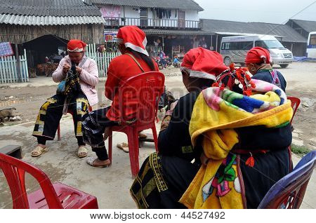 Red Dao women sewing clothes for tourists in Sa Pa, Vietnam
