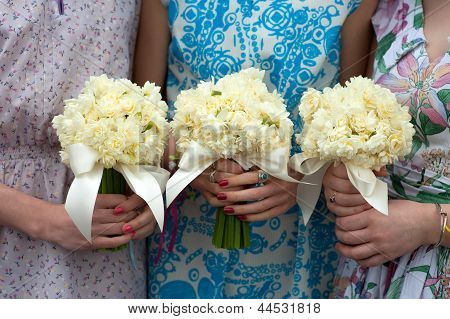 Three Daffodil Wedding Bouquets Held By Bridesmaids