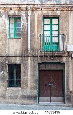 Facade With Metal Door, Windows And Balcony