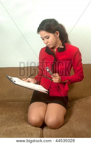 Asian Woman Wearing Red Suit Holding A Clipboard And Looking By Magnifying Glass On Sofa .