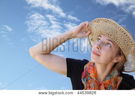 A Woman In A Hat With Interest Looks Up At The Blue Sky
