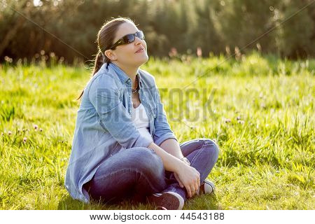 Smiling Woman Sunbathing Sitting In A Field