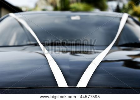 wedding car with white ribbon