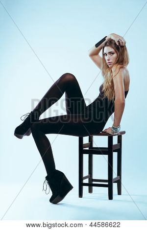 Blonde In Black Swimsuit Sitting On Chair Posing Studio
